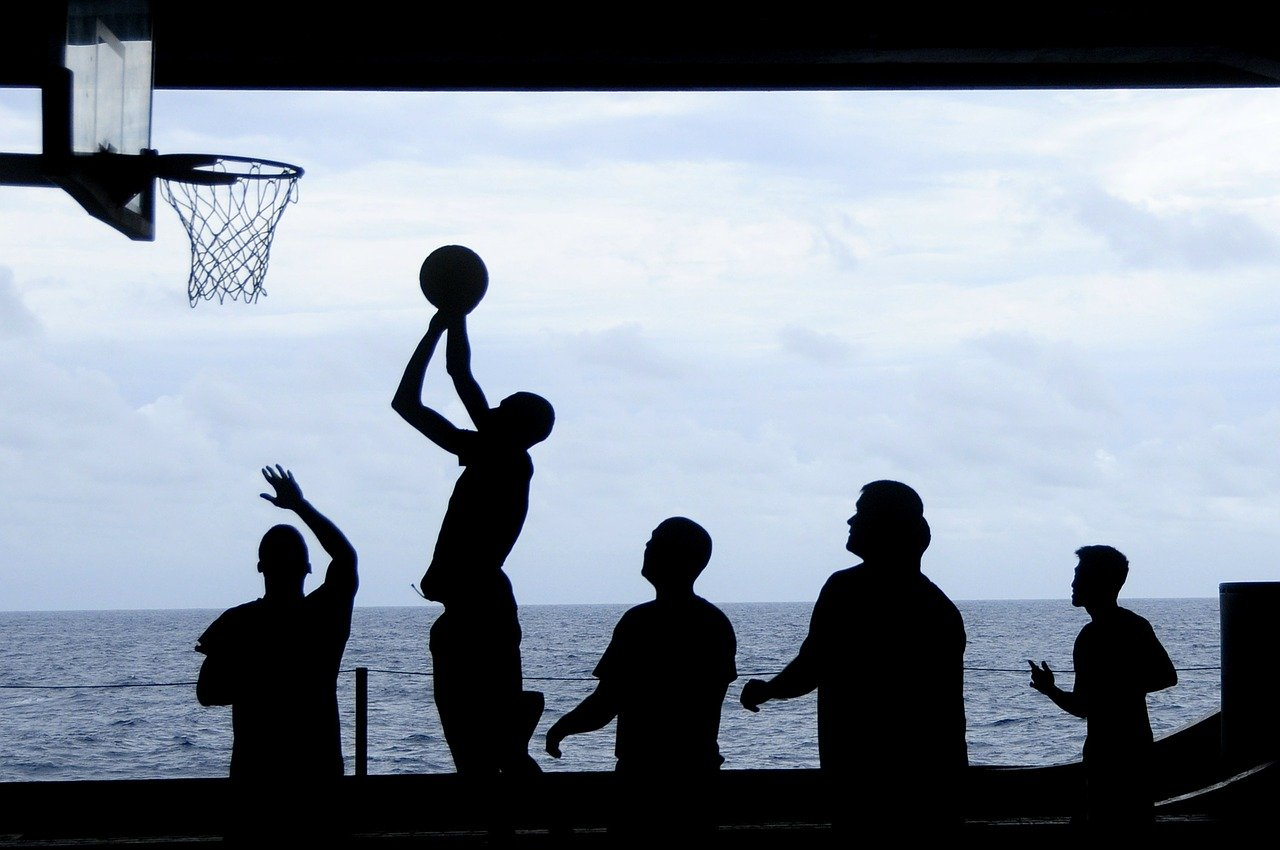Basket ball game being played in silhouette