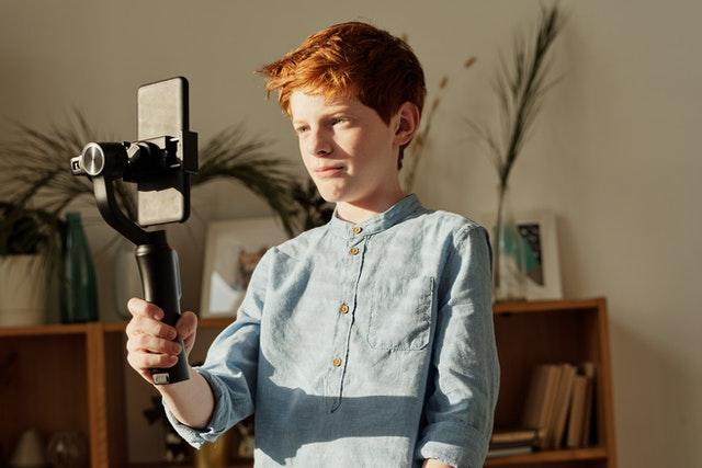 Teenage boy making a film