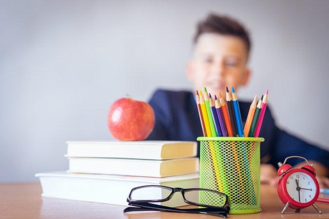 boy sitting behind school materials