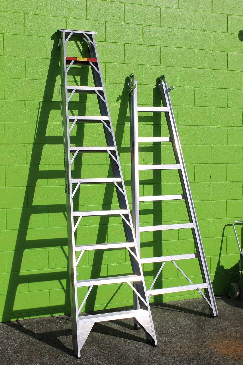 two sets of ladders resting against a green wall