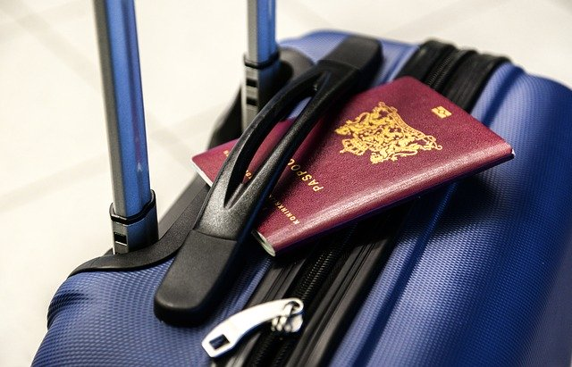 Passport tucked in to the strap of a suitcase