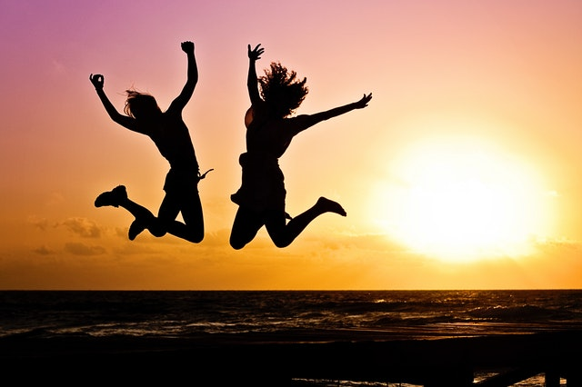 two young people jumping joyfully in front of a sunset