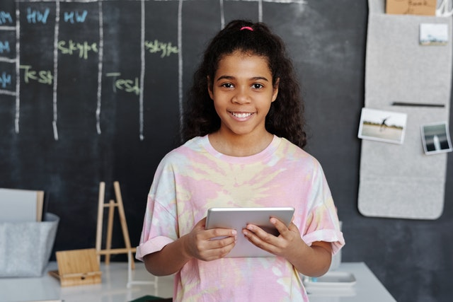 Happy girl in front of a chalk board